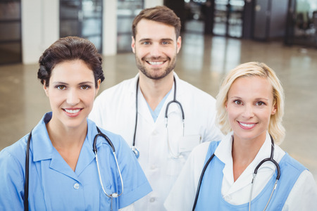 High angle portrait of smiling doctors and nurse standing at hospital