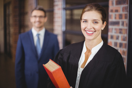 female lawyer: Portrait of happy female lawyer with businessman standing in background