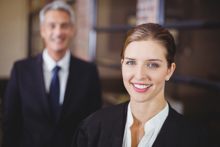 female lawyer: Close-up portrait of female lawyer smiling while male colleague in background Stock Photo