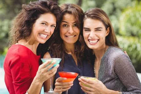 clenching teeth: Close-up of beautiful female friends making face while drinking cocktail at party Stock Photo