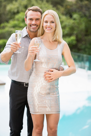 champagne flutes: Portrait of smiling couple showing champagne flutes at poolside Stock Photo