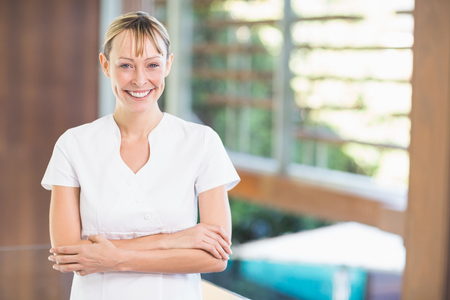 Portrait of happy female masseur with arms crossed standing at health spa
