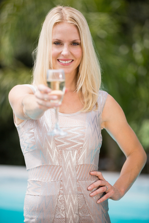 champagne flute: Portrait of happy woman offering champagne flute while standing at poolside