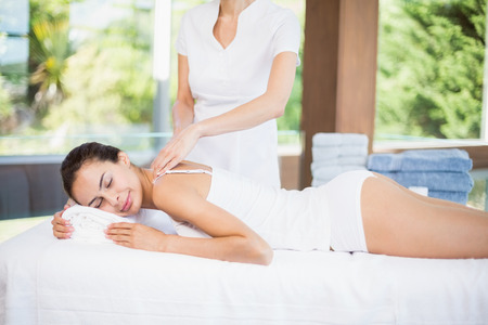 masseur: Young woman receiving massage from female masseur at spa Stock Photo