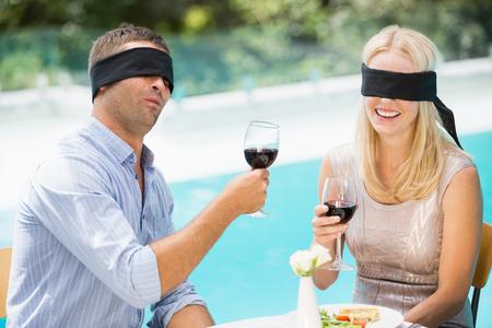 ojos vendados: pareja con los ojos vendados que sostiene el vino tinto mientras que se sienta en la piscina