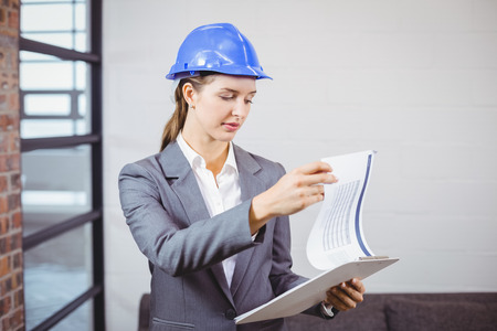 female architect: Female architect checking documents while standing in building