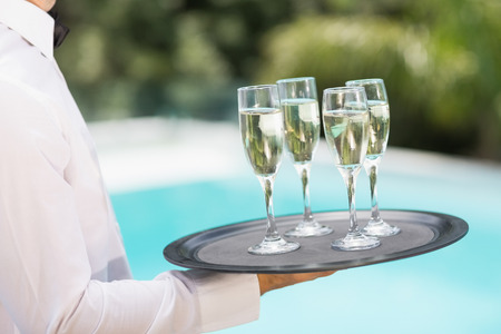 champagne flutes: Midsection of waiter carrying champagne flutes on tray at poolside