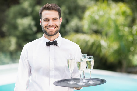 champagne flutes: Portrait of smiling waiter carrying champagne flutes on tray at poolside Stock Photo