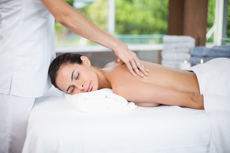 masseur: Young woman receiving back massage from female masseur at health spa