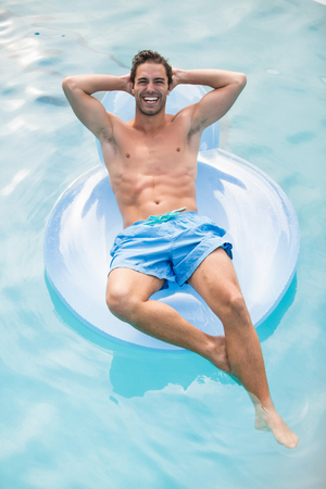 getting away from it all: Happy shirtless man relaxing on inflatable ring in swimming pool Stock Photo