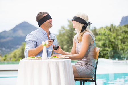 ojos vendados: Blindfolded couple holding red wine while sitting by swimming pool at resort