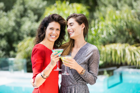 friendliness: Cheerful young female friends drinking cocktail by swimming pool during party Stock Photo