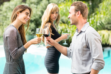 toasting wine: Jealous woman looking at happy couple toasting wine during party