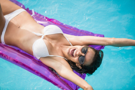 getting away from it all: Cheerful young woman swimming with inflatable raft at pool