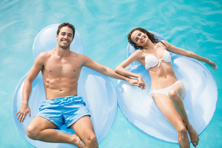 away from it all: Portrait of happy couple relaxing on inflatable ring at swimming pool