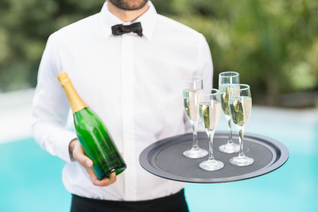 champagne flutes: Midsection of waiter holding champagne flutes and bottle at poolside