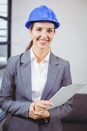 female architect: Portrait of smiling female architect standing in building