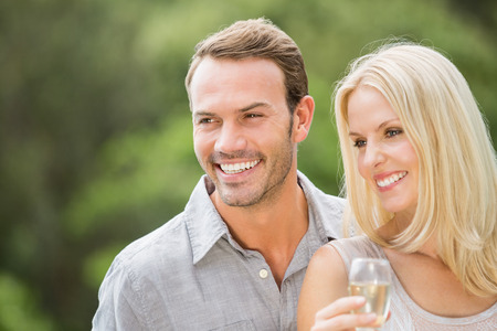 champagne flute: Smiling couple looking away with woman holding champagne flute
