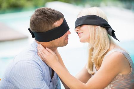 ojos vendados: Con los ojos vendados pareja bes�ndose mientras est� sentado en la piscina