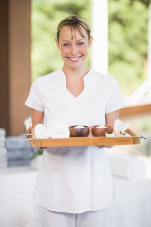 masseur: Portrait of happy female masseur holding tray with spa therapy products