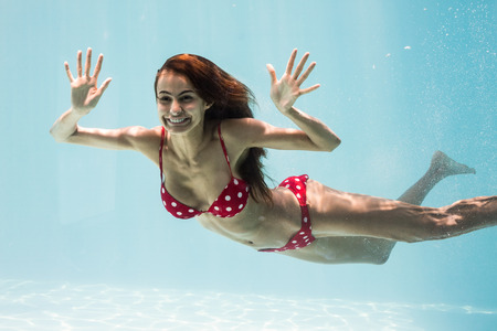 escapism: Cheerful young woman swimming underwater Stock Photo