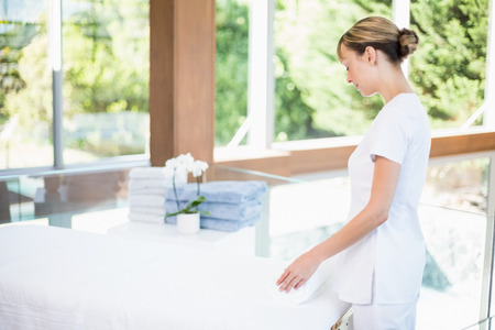 masseur: Female masseur rolling towel on massage table at health spa Stock Photo