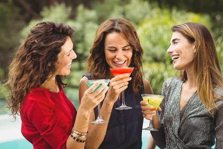 trato amable: Hermoso de los amigos femeninos que r�en mientras que bebe el coctel en la fiesta