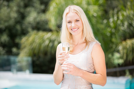 champagne flute: Portrait of smiling woman holding champagne flute while standing at poolside