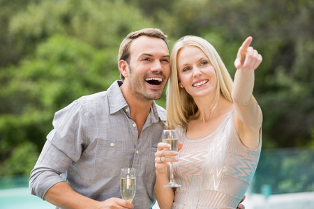 champagne flute: Smiling woman pointing while standing by man holding champagne flute at poolside Stock Photo