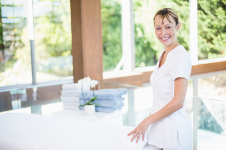 Portrait of happy female masseur rolling towel on massage table at spa