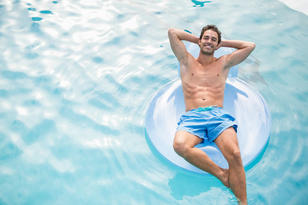 getting away from it all: High angle view of shirtless man relaxing on inflatable ring in swimming pool