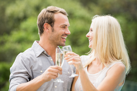 flutes: Smiling couple toasting champagne flutes at resort