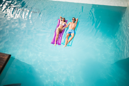 getting away from it all: High angle view of couple relaxing on inflatable raft at swimming pool Stock Photo