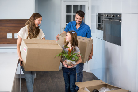 Smiling family moving house with boxes