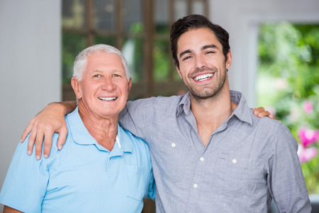 senior adult man: Portrait of smiling father and son with arm around wile standing at home