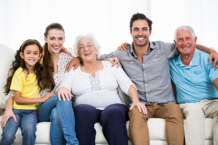 family sofa: Portrait of smiling family with arm around while sitting on sofa at home
