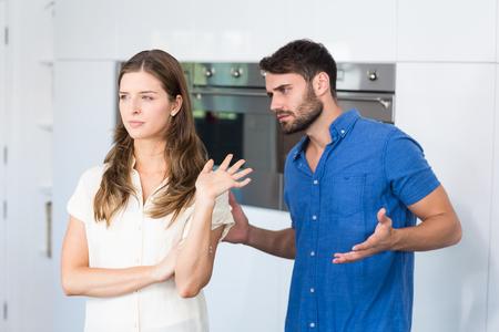 Uomo che spiega a sconvolgere moglie in cucina a casa