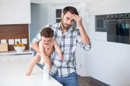 bambino che piange: Ritratto del padre frustrato tenendo pianto bambino da tavolo a casa