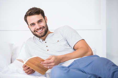 man holding book: Portrair of smiling man holding book on bed at home