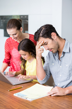 tensed: Daughter and mother working on laptop with tensed father sitting at desk in home Stock Photo