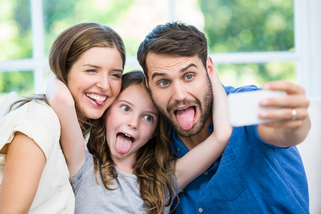 making faces: Happy family making faces while clicking selfie at home