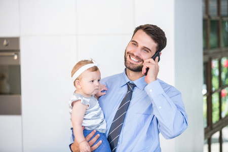 multi family house: Happy businessman talking on mobile phone while carrying daughter at home Stock Photo