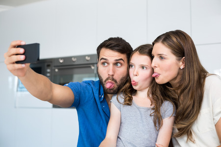 sacar la lengua: Family sticking out tongue while clicking selfie at home