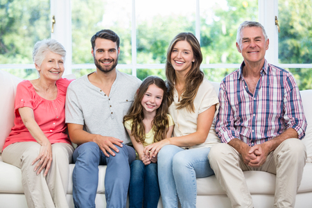 family sofa: Portrait of happy family sitting on sofa at home Stock Photo