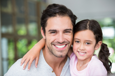 arm around: Portrait of smiling father and daughter with arm around at home Stock Photo
