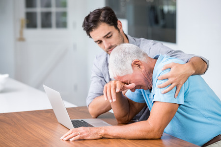 tensed: Son comforting tensed father sitting at desk with laptop Stock Photo