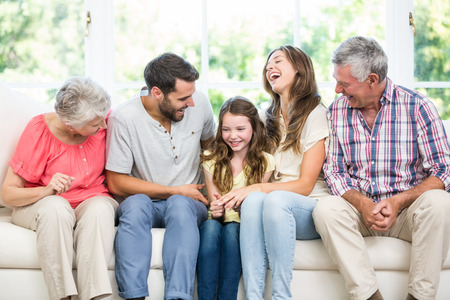 family sofa: Cheerful family sitting on sofa at home Stock Photo