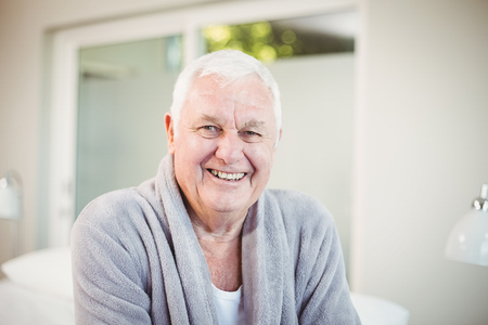 Portrait of happy senior man in bedroom at home Stock Photo