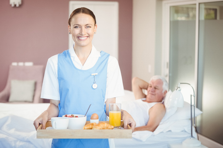old people care: Portrait of cheerful nurse with tray standing while senior man lying in background