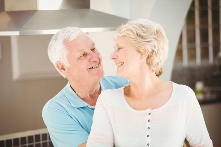 active life: Active senior couple embracing in kitchen at home